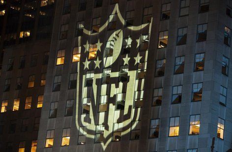 A man stands at a window lit by the NFL logo as he watches performances during the 2012 NFL kickoff show in New York September 5, 2012. REUT