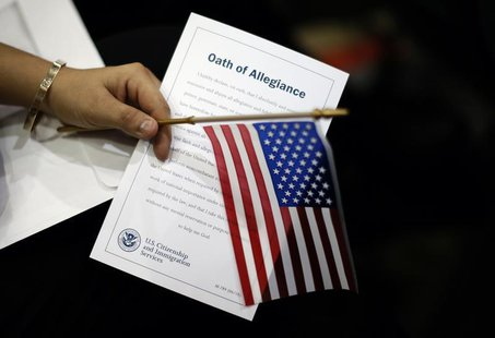 A woman holds the Oath of Allegiance at a naturalization ceremony for 3,703 new U.S. citizens from 130 countries, in Los Angeles, California