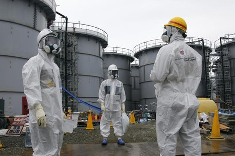 Tokyo Electric Power Corp's (TEPCO) official (C) and journalists wearing protective suits and masks stand in front of storage tanks for radi