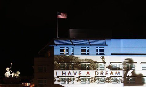 A light installation showing Martin Luther King Jr. is projected on the facade of the U.S. Embassy, next to the Quadriga (L) atop of the Bra