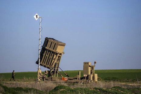 An Israeli soldier walks near the launcher of an Iron Dome missile interceptor battery deployed in the southern Israeli coastal city of Ashk