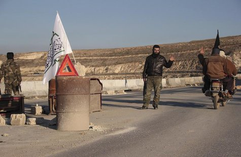 A member of al-Jabha al-Islamiya (the Islamic Front) mans a checkpoint between the village of Kafaroumeh and the town of Maaret al-Naaman, t