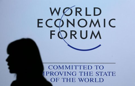 A delegate is silhouetted as she passes by a sign for the annual meeting of the World Economic Forum (WEF) in Davos January 26, 2013. REUTER