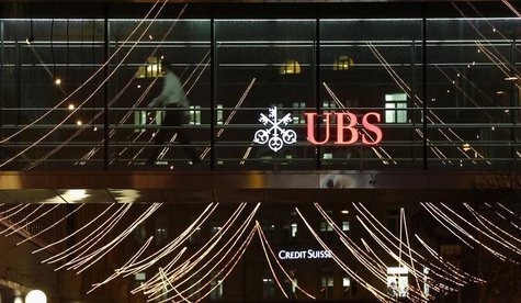 A man walks past the logo of Swiss Bank UBS on a footbridge connecting two office buildings in Zurich December 19, 2013. REUTERS/Arnd Wiegma