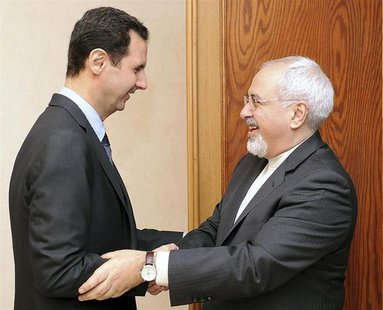 Syria's President Bashar al-Assad (L) welcomes Iran's Foreign Minister Mohammad Javad Zarif before a meeting in Damascus January 15, 2014, i