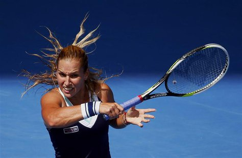 Dominika Cibulkova of Slovakia hits a return to Maria Sharapova of Russia during their women's singles match at the Australian Open 2014 ten