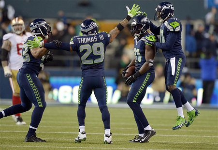 Jan 19, 2014; Seattle, WA, USA; Seattle Seahawks strong safety Kam Chancellor (31) celebrates with his teammates after making an interceptio