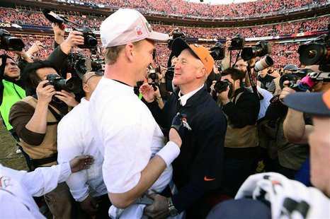 Denver Broncos quarterback Peyton Manning (18) and head coach John Fox celebrate the 26-16 victory against the New England Patriots followin