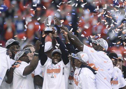 Denver Broncos players hold up the Lamar Hunt Trophy after they defeated the New England Patriots in the NFL's AFC Championship football gam