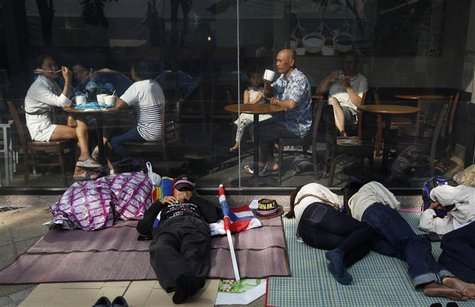 Anti-government protesters sleep in front of a coffee shop in central Bangkok January 20, 2014. REUTERS/Paul Barker