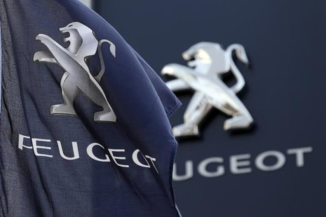 A flag with the company logo is seen outside a Peugeot automobile dealer in Paris December 13, 2013. REUTERS/Charles Platiau