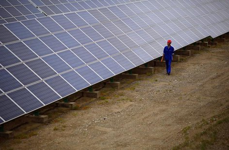 A worker inspects solar panels at a solar farm in Dunhuang, 950km (590 miles) northwest of Lanzhou, Gansu Province September 16, 2013. 26.RE