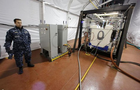 The Field Deployable Hydrolysis System used to destroy and neutralize chemical weapons is watched by U.S. Navy Commander Bill Speaks as it s