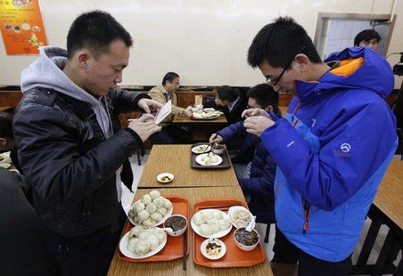 Diners take pictures of steamed buns which Chinese President Xi Jinping ate on Saturday, at the Qing-Feng steamed buns restaurant in Beijing