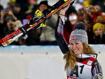 Mikaela Shiffrin from the U.S. celebrates with the trophy after winning the World Cup women's slalom race in Flachau January 14, 2014. REUTE