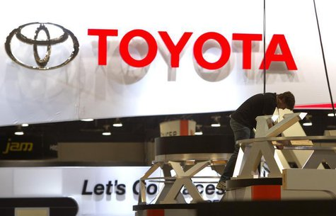 A worker sets up a display near the Toyota booth in preparation for the 2014 Consumer Electronics Show (CES) at the Las Vegas Convention Cen