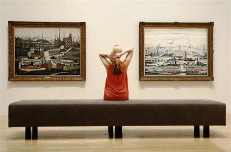 A file photograph shows a Tate employee posing for a photograph with works by British artist L.S.Lowry at Tate Britain in London June 24, 20
