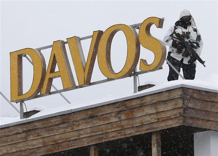 A Swiss special policeman patrols on a roof before the start of the annual meeting of the World Economic Forum (WEF) 2014 in Davos January 2
