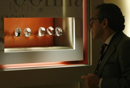 "A visitor looks at watches at the Parmigiani booth during the opening day of the ""Salon International de la Haute Horlogerie"" at Palexpo in"
