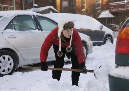 Jessica Corner shovels snow so she can move her vehicle from behind the apartment building she lives in during bitter cold temperatures in D