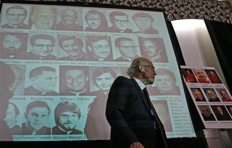Attorney Jeff Anderson walks by a projection of photographs of priests at a news conference where thousands of documents on victims of sexua