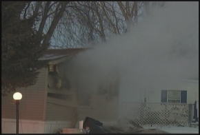 Smoke is seen, drifting out of the window of the mobile home