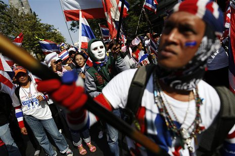 Anti-government protesters wave flags as they march through Bangkok's financial district January 21, 2014. REUTERS/Damir Sagolj