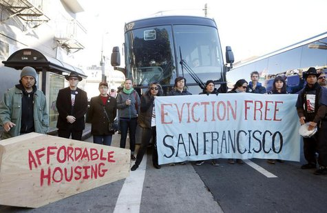 Protesters block a bus full of Apple employees during a protest against rising costs of living in San Francisco, California, December 20, 20