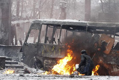 Pro-European protesters take cover behind a burnt bus during clashes with riot police in Kiev January 22, 2014. REUTERS/Vasily Fedosenko