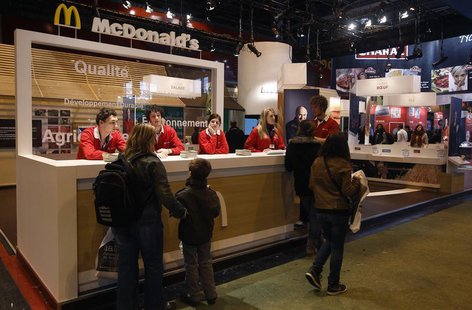 People walk past a McDonald's fast food stand at the 49th Paris International Farm Show at the Porte de Versailles exhibition center in Pari