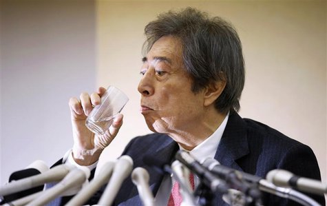Japan's former Prime Minister Morihiro Hosokawa drinks water as he officially announces his bid to run for Tokyo governor during a news conf