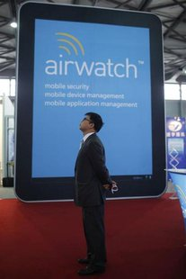 A man stands near an AirWatch display at the Mobile Asia Expo in Shanghai June 20, 2012. REUTERS/Aly Song