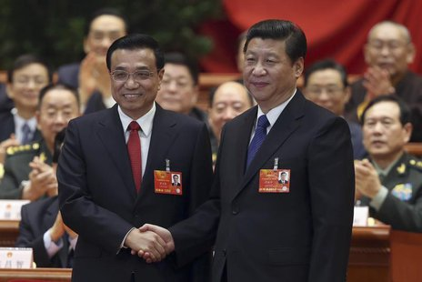 China's President Xi Jinping shakes hands with China's newly elected Premier Li Keqiang (L) as other delegates clap during the fifth plenary