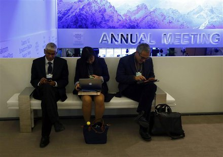 Participants use their smart phones and laptops as they sit on a bench between sessions during the annual meeting of the World Economic Foru