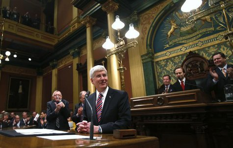 Michigan's Governor Rick Snyder (C) is acknowledged by the Assembly before his annual State of the State address at the State Capitol in Lan