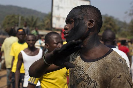 A man with charcoal smeared on his face reacts as a crowd barricades a street during a dispute between members of the local Christian commun