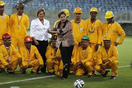 Brazil's President Dilma Rousseff (C) kicks the ball while standing near workers during the opening ceremony of the Arena das Dunas stadium,