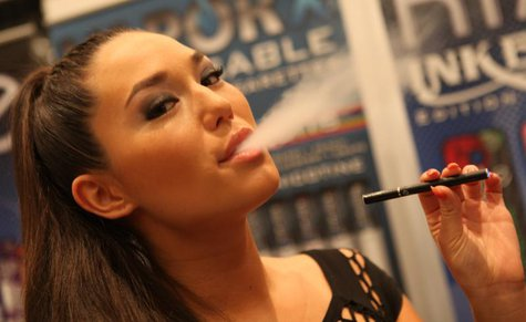 "A woman ""smokes"" an e-cigarette."