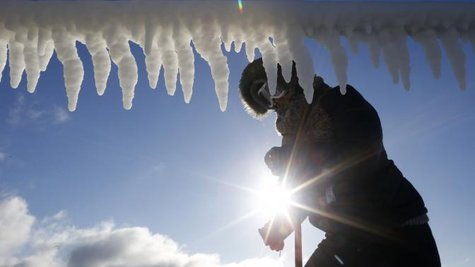 A woman is seen by icicles hanging from a breakwater along a beach in Chicago, Illinois, January 21, 2014.  CREDIT: REUTERS/JIM YOUNG
