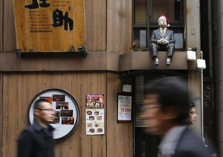 A lifesized doll, adorned with a Santa hat, is seen above the doorway of a restaurant as people walk along a street at Tokyo's Shinjuku shop