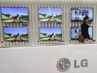 A customer talks in front of LG 3D TV sets which are made with LG Display flat screens, at a store in Seoul January 23, 2013. REUTERS/Kim Ho