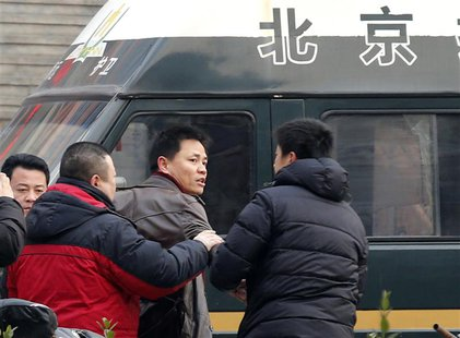 Zhang Xuezhong (C), a lawyer for Chinese dissident Zhao Changqing, argues with plain-clothed policemen as he refuses to show them his identi