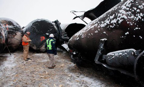 National Transporation and Safety Board (NTSB) member Robert Sumwalt (R) views damaged rail cars at the scene of the BNSF train accident in