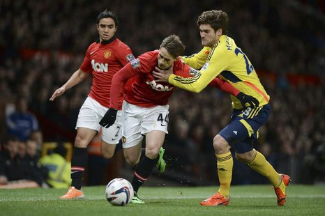 Manchester United's Adnan Januzaj (C) challenges Sunderland's Marcos Alonso during their English League Cup semi-final second leg soccer mat