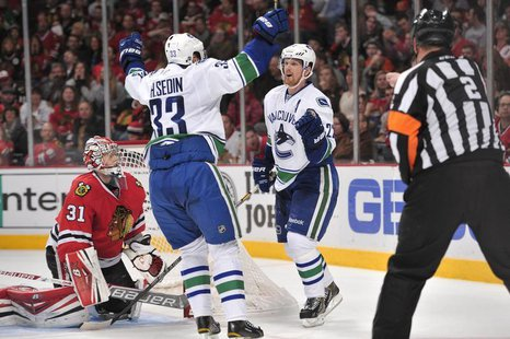 Dec 20, 2013; Chicago, IL, USA; Vancouver Canucks left wing Daniel Sedin (22) celebrates with center Henrik Sedin (33) after scoring a goal