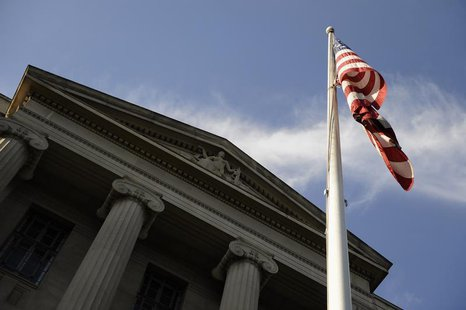 A US flag flies outside the U.S. Department of Justice headquarters building in Washington, July 14, 2009. REUTERS/Jonathan Ernst
