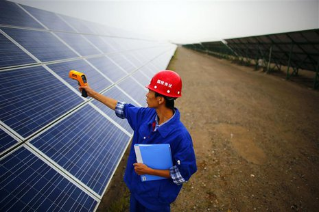 A worker inspects solar panels at a solar farm in Dunhuang, 950km (590 miles) northwest of Lanzhou, Gansu Province September 16, 2013. REUTE