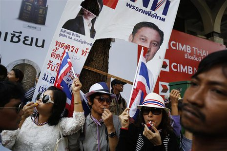 Under a damaged pre-election poster of Thai Prime Minister Yingluck Shinawatra, anti-government protesters blow whistles as they greet fello