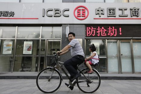A man and his daughter ride a bicycle past a branch of the Industrial and Commercial Bank of China Ltd (ICBC) in Beijing June 26, 2013. REUT