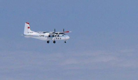 A Chinese government plane Y-12 flies about 120km (75 miles) north of the the disputed isles, known as Senkaku isles in Japan and Diaoyu isl